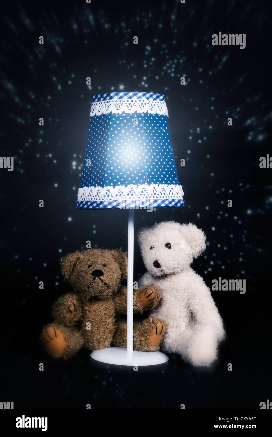two teddy bears are sitting under an old vintage lamp - Stock Image