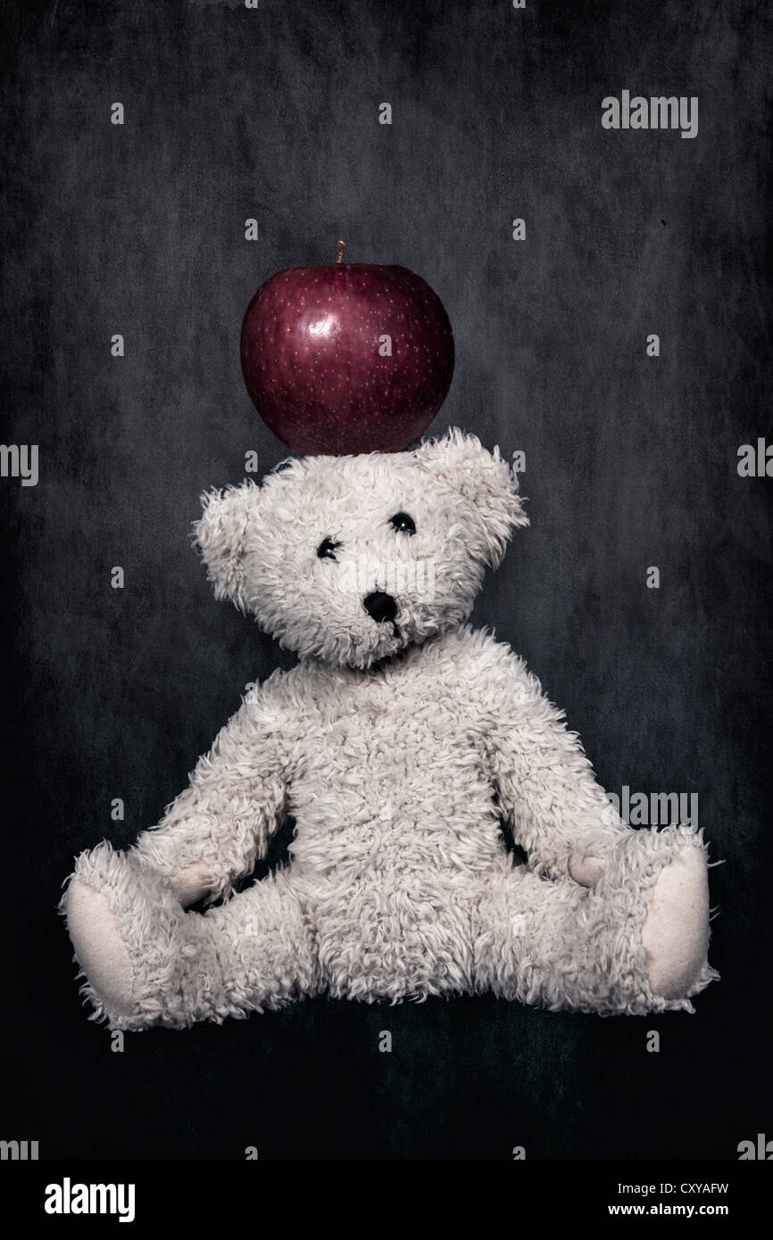a white teddy bear with a red apple on the head - Stock Image