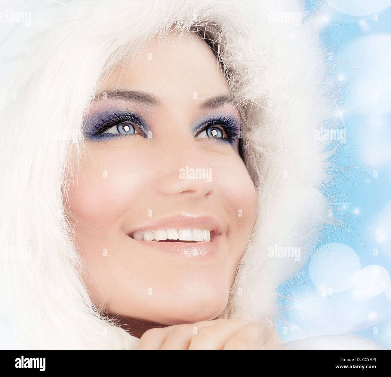 Snow queen, beautiful woman in Christmas style makeup, female portrait over blue holiday background with shiny glowing - Stock Image