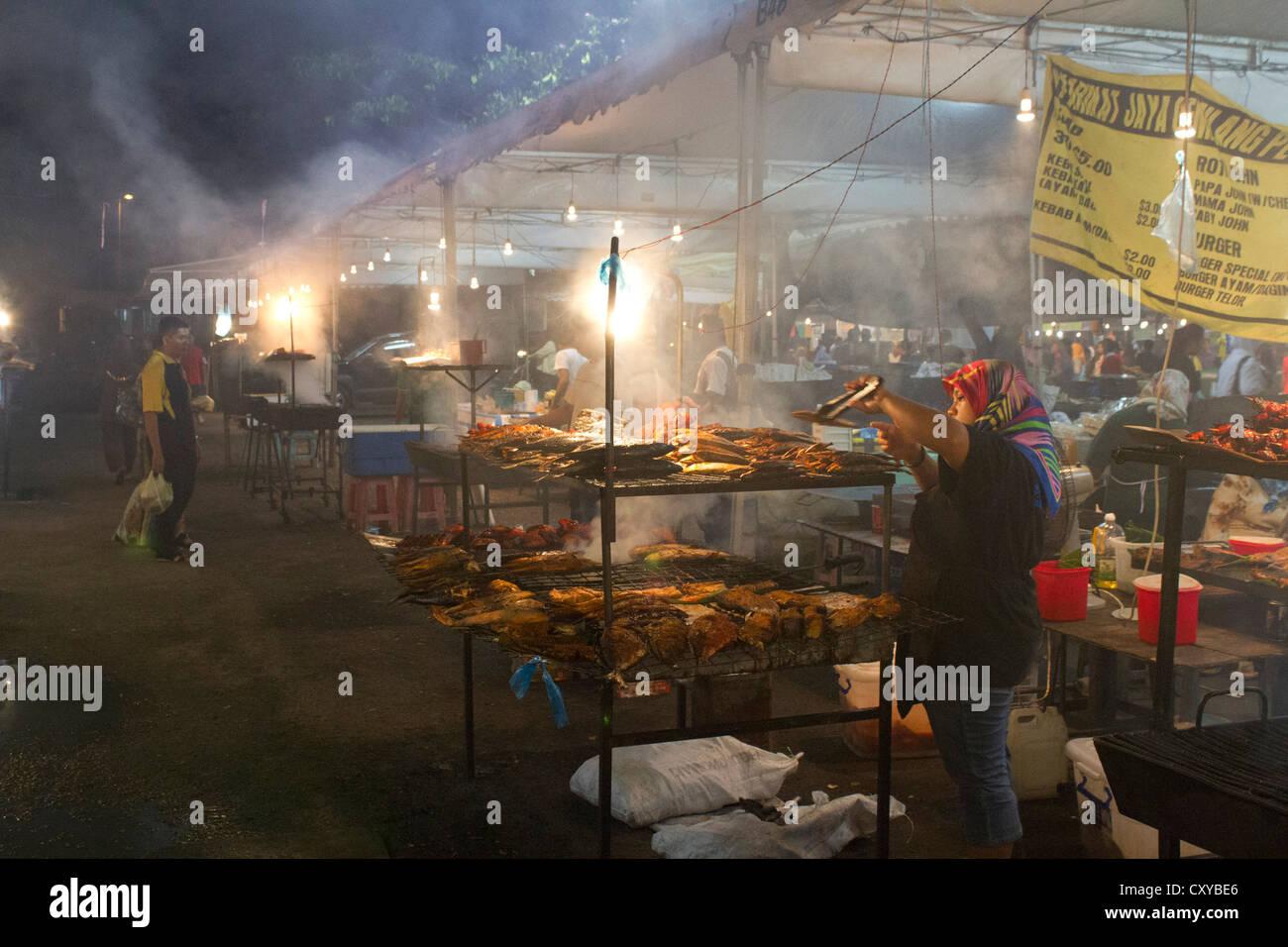 Brunei night market smoking fish - Stock Image