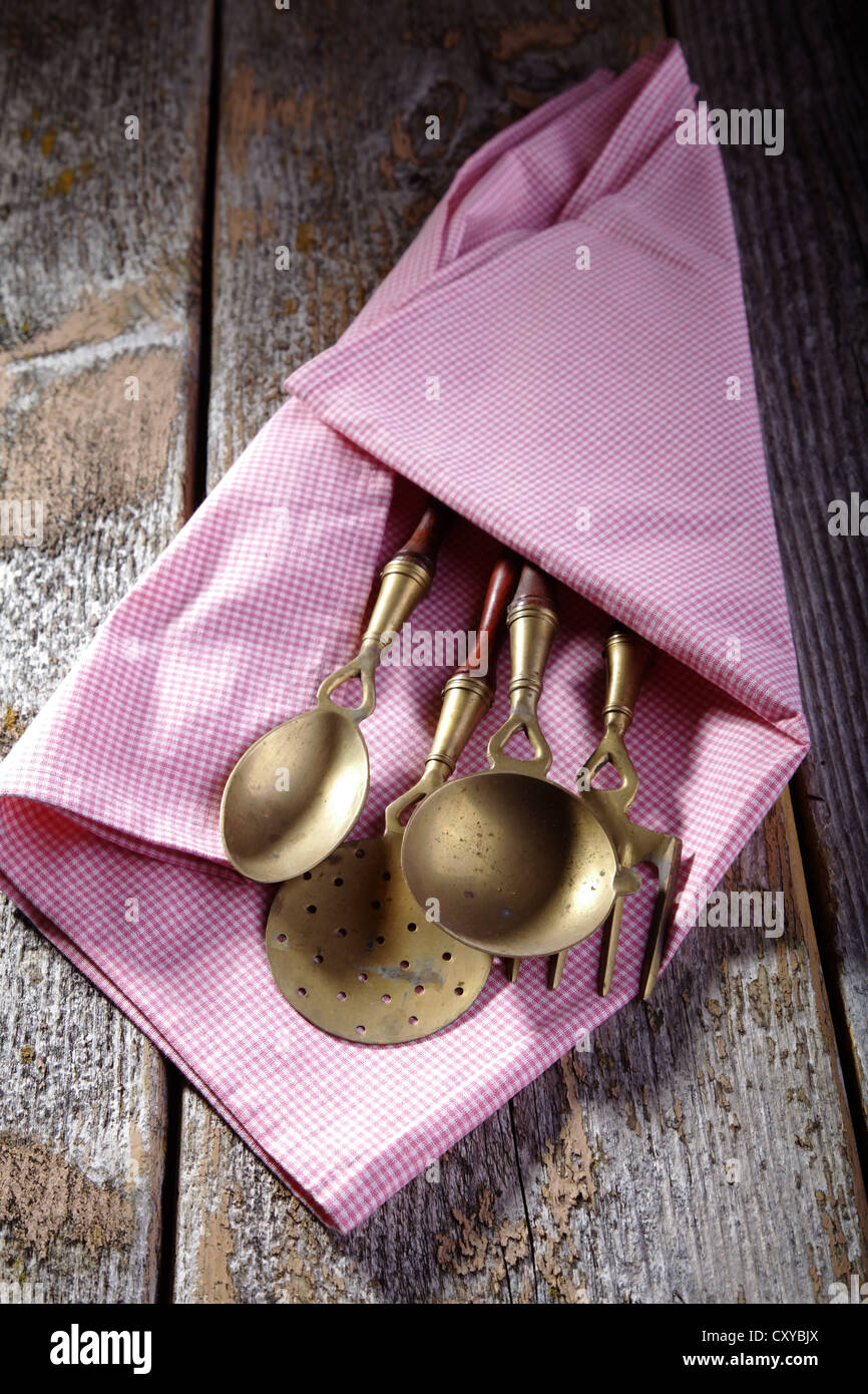Old kitchen utensils made of brass wrapped in a kitchen towel, lying on a rustic wooden background - Stock Image