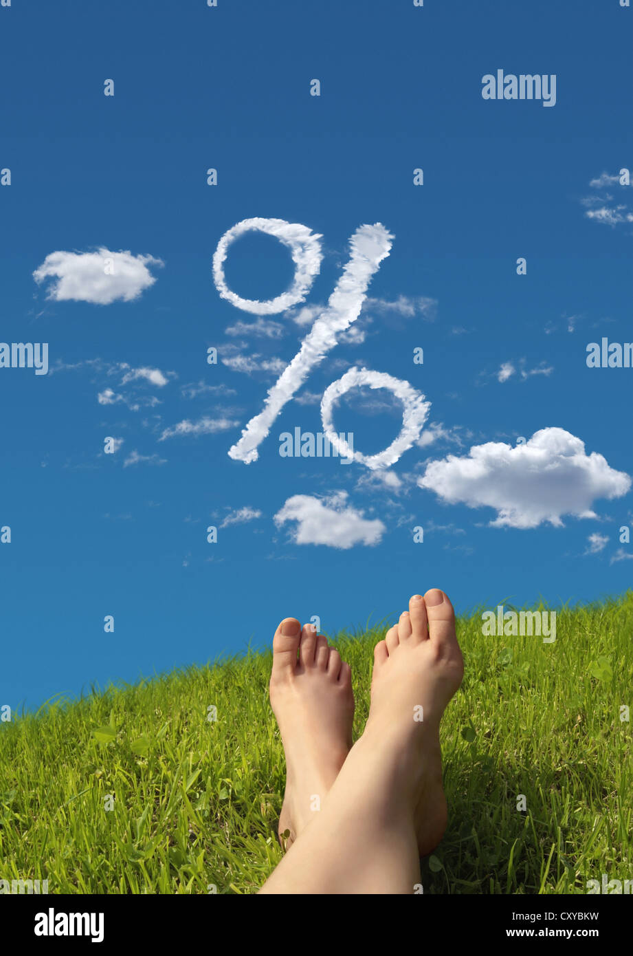 Woman lying on a meadow, detail of feet with a cloud formation shaped like a percent symbol in the sky - Stock Image
