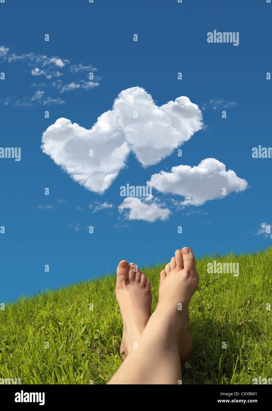 Woman lying on a meadow, detail of feet with a heart-shaped cloud formation in the sky - Stock Image