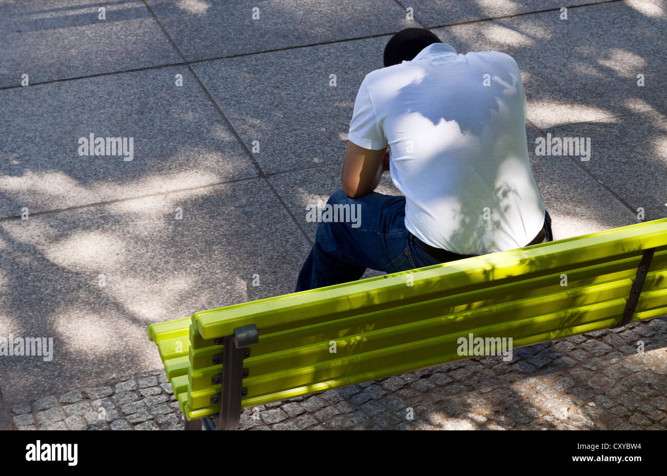 Man with bowed head sitting on a green park bench, Berlin - Stock Image