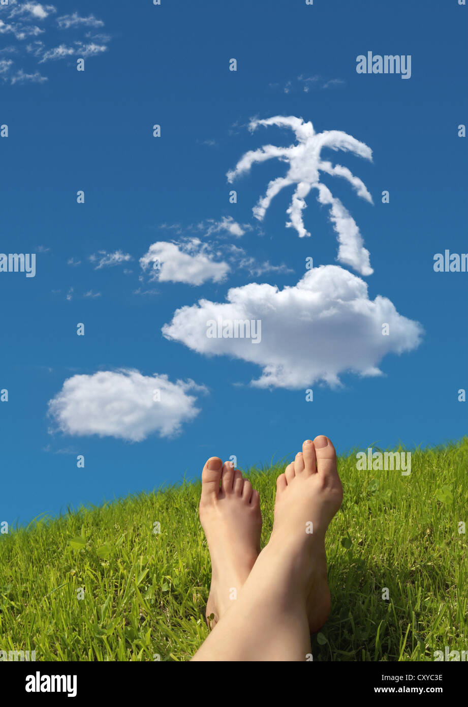 Woman lying on a meadow, detail of feet with a cloud formation shaped like a tropical island in the sky - Stock Image