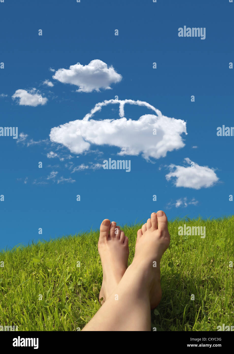 Woman lying on a meadow, detail of feet with a car-shaped cloud formation in the sky - Stock Image