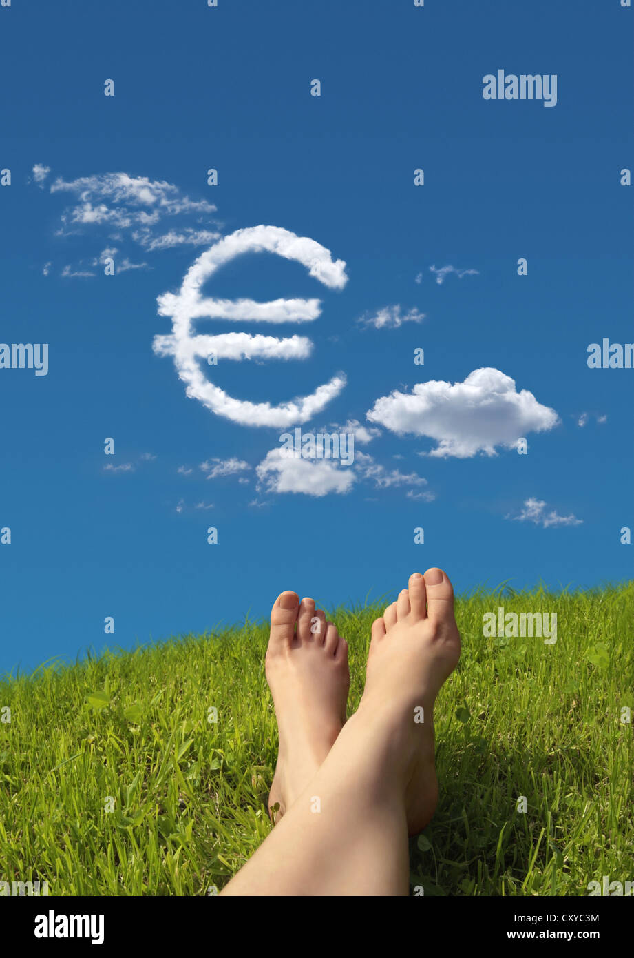 Woman lying on a meadow, detail of feet with a cloud formation shaped like a euro symbol in the sky - Stock Image