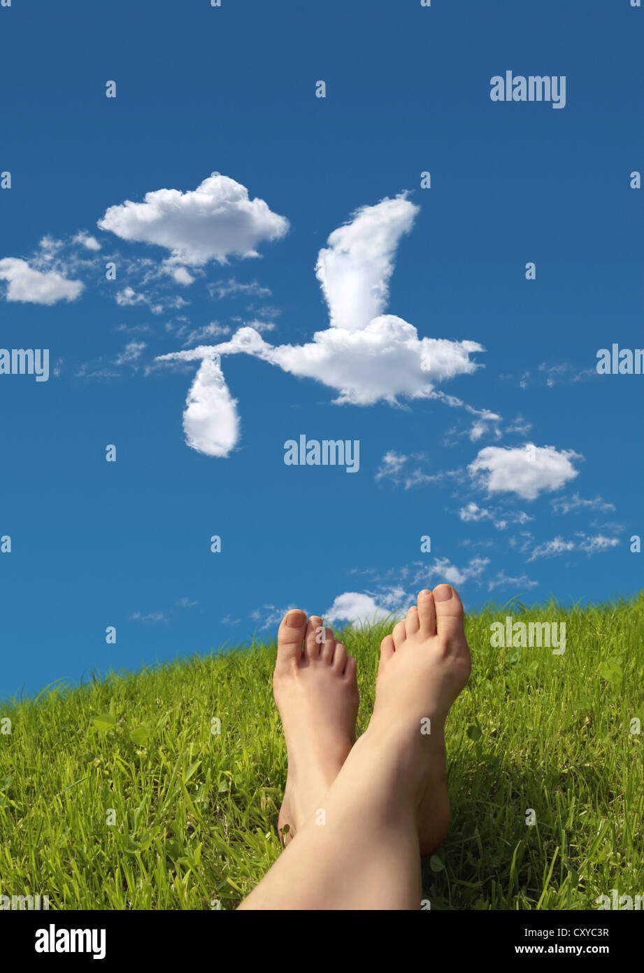 Woman lying on a meadow, detail of feet with a cloud formation shaped like a stork carrying a baby in the sky - Stock Image