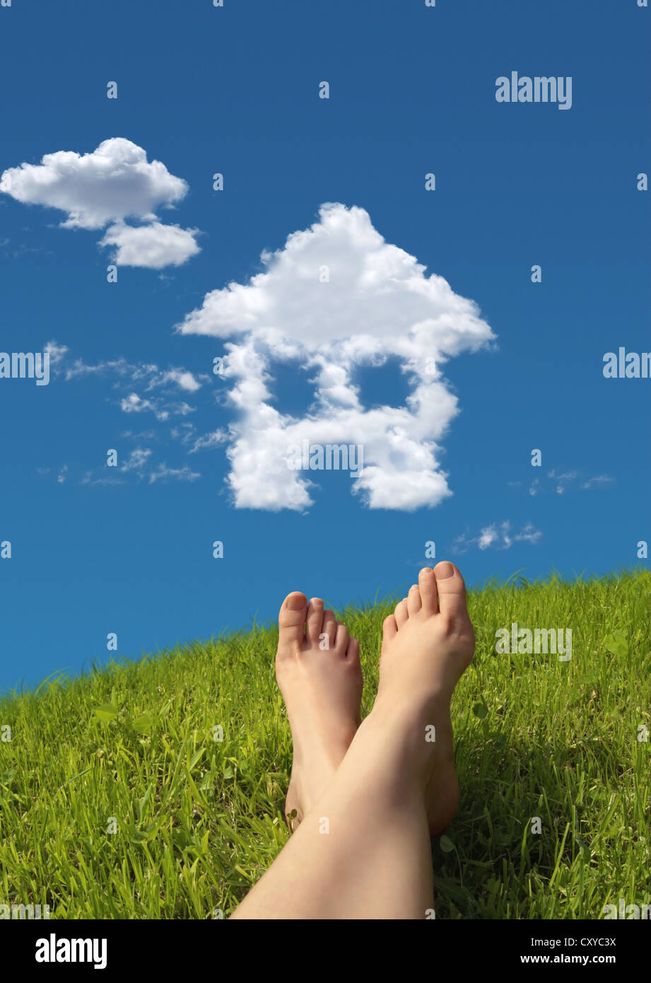 Woman lying on a meadow, detail of feet with a house-shaped cloud formation in the sky - Stock Image