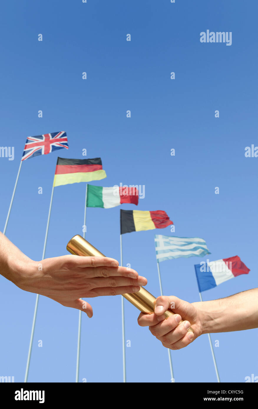 Relay race, detail of athletes hands during the handover of the baton in front of international flags - Stock Image