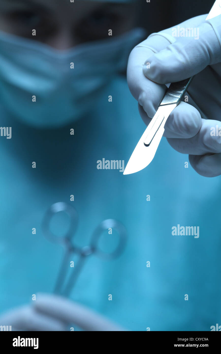 Surgery, surgeon's hand holding a scalpel - Stock Image