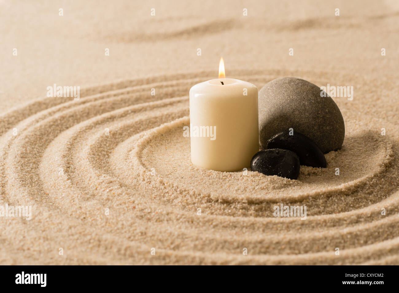 Spa atmosphere candle with zen stones in sand still nature - Stock Image