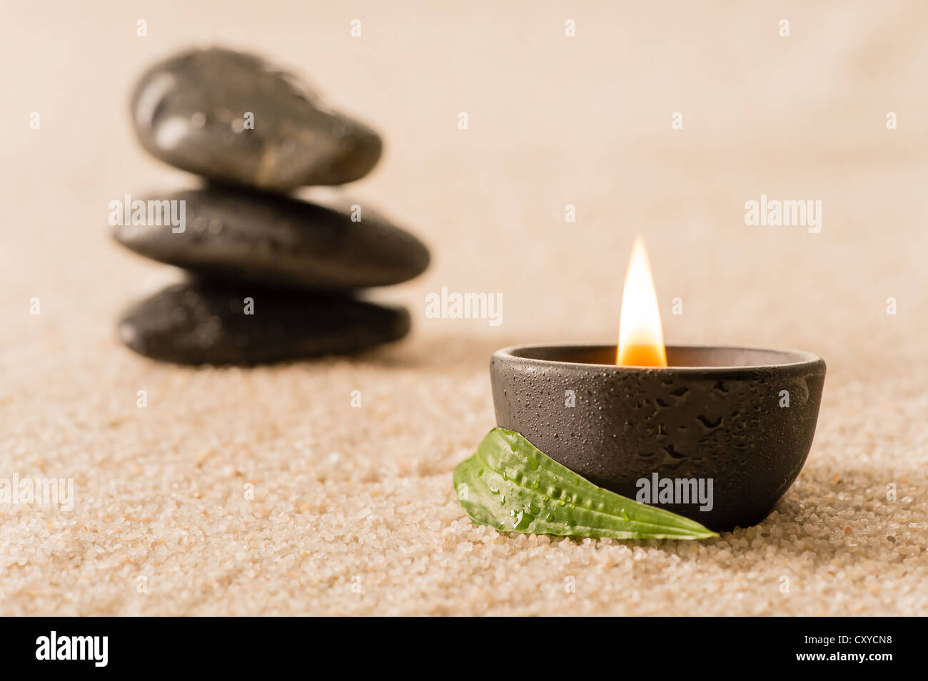 Spa still life burning candle with zen stones - Stock Image
