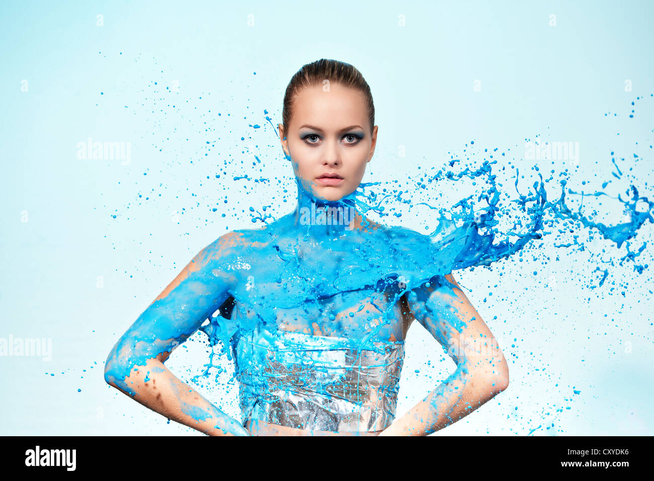 Blue paint being thrown at a young woman - Stock Image