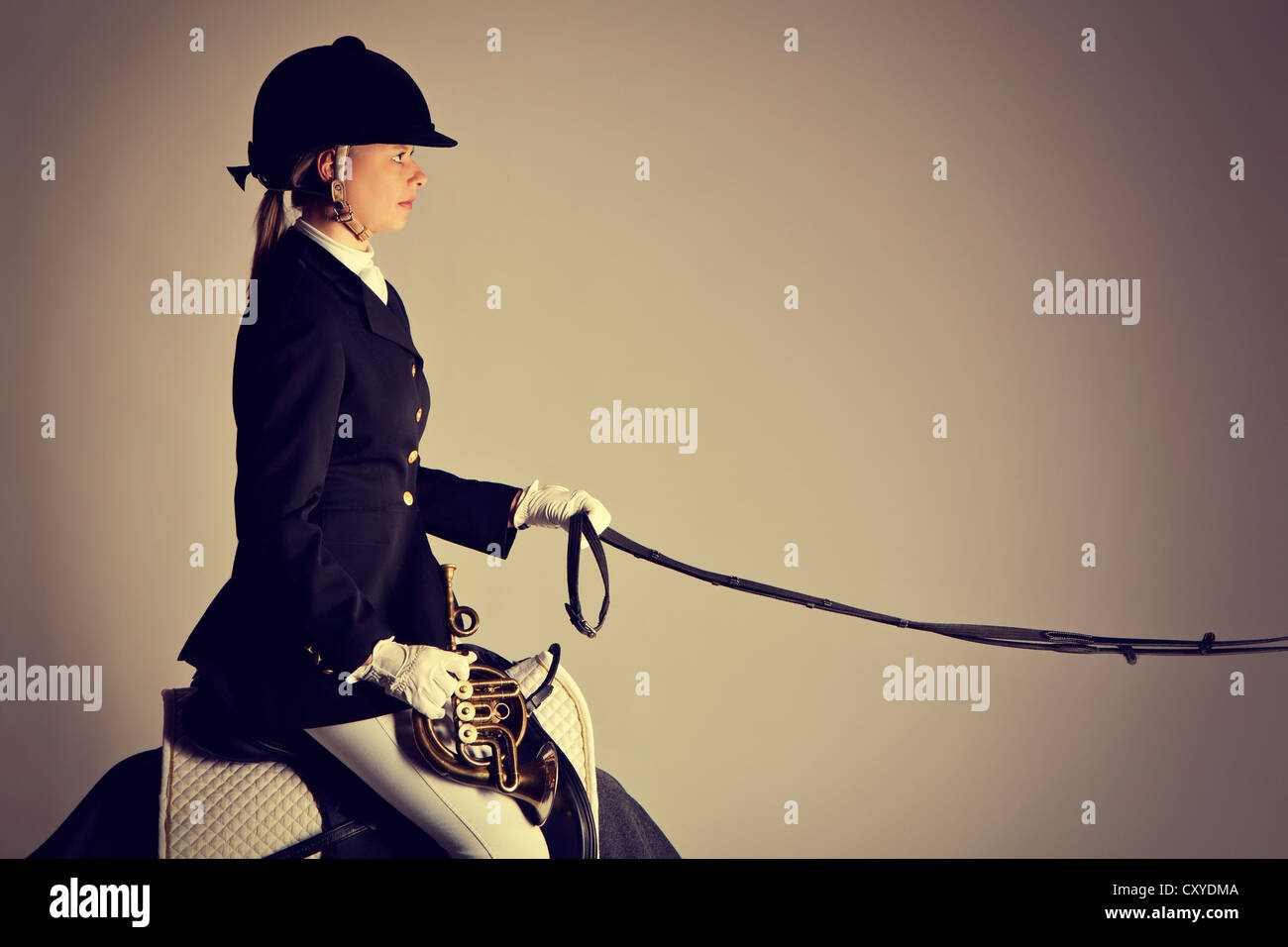 Female rider without a horse holding a posthorn - Stock Image