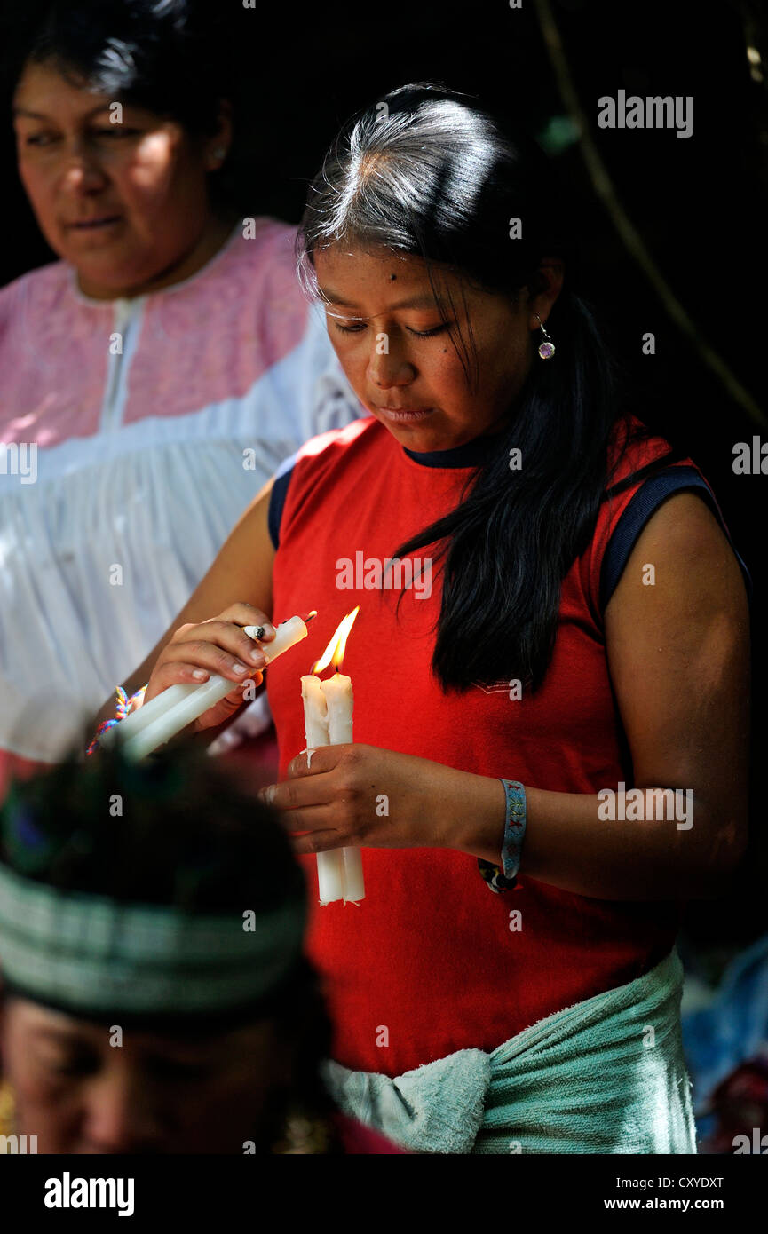 Young woman lighting candles at traditional ablutions to ward off evil spirits and to cleanse the soul of the indigenous - Stock Image