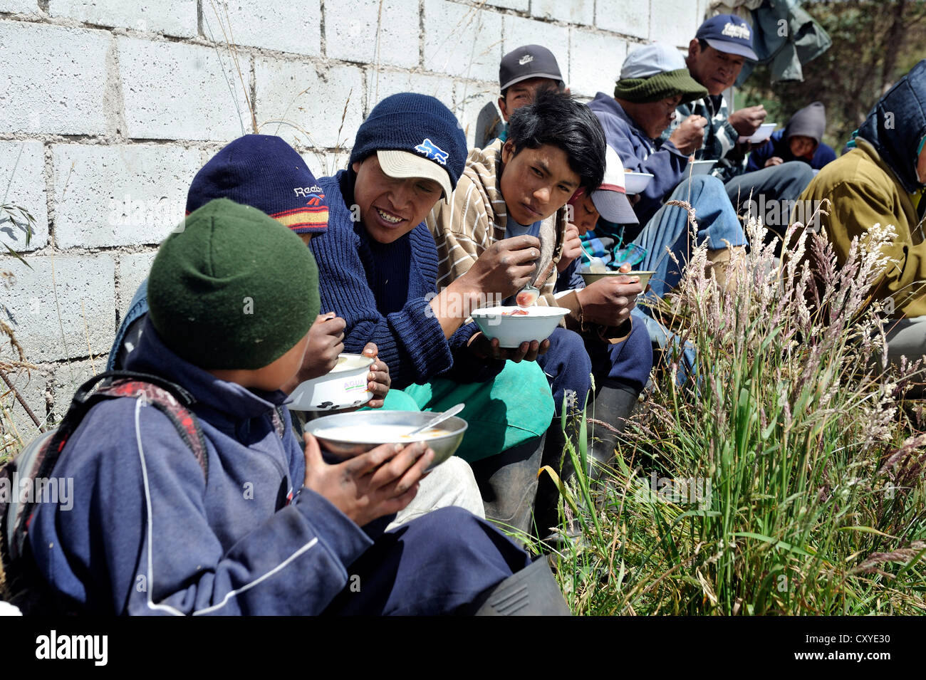Volunteers doing voluntary community work, Minga, being fed, eating soup, after the installation of a fresh water - Stock Image