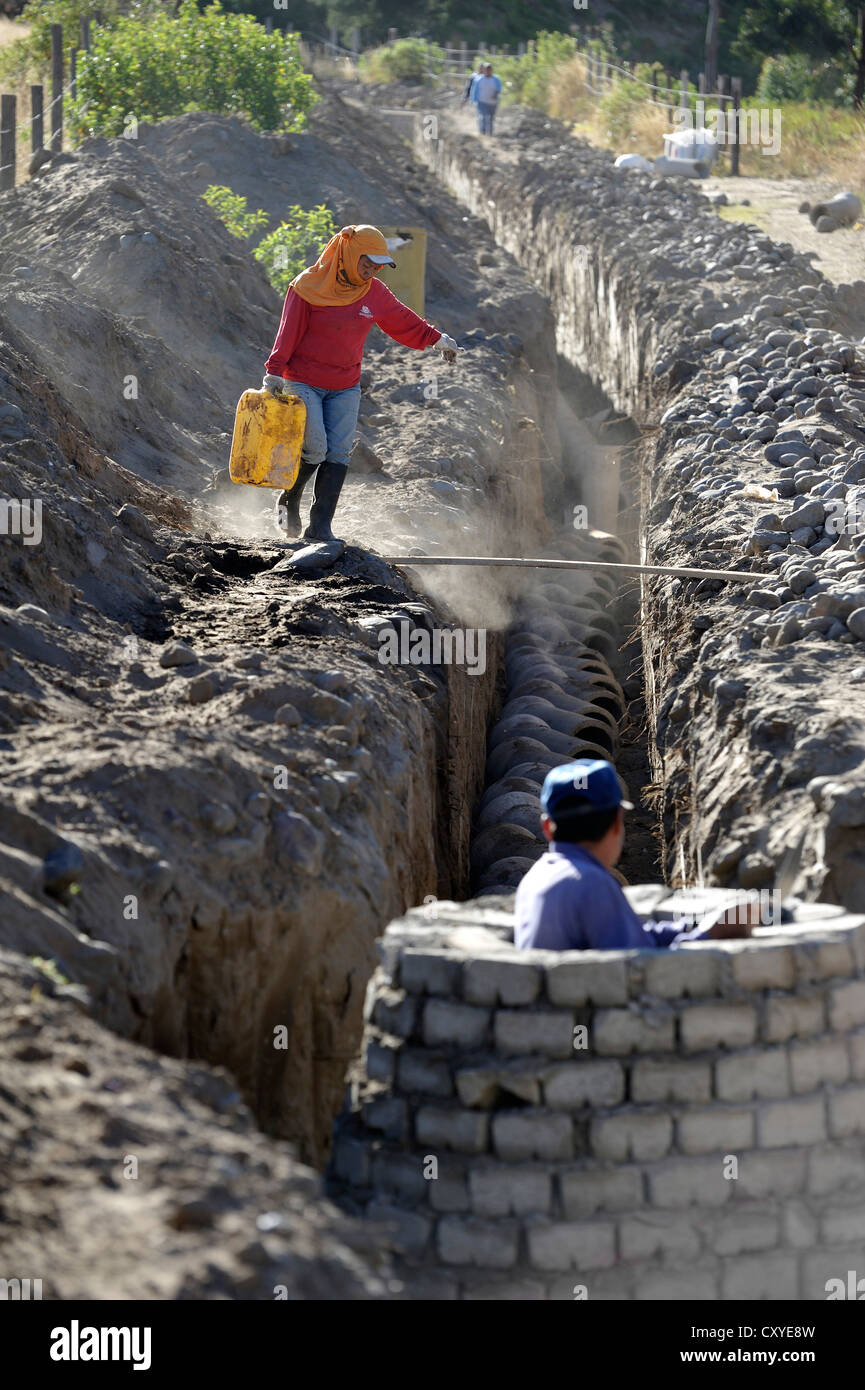 Construction of a drain for the sewer system, carried out through voluntary community work, Minga, by members of - Stock Image
