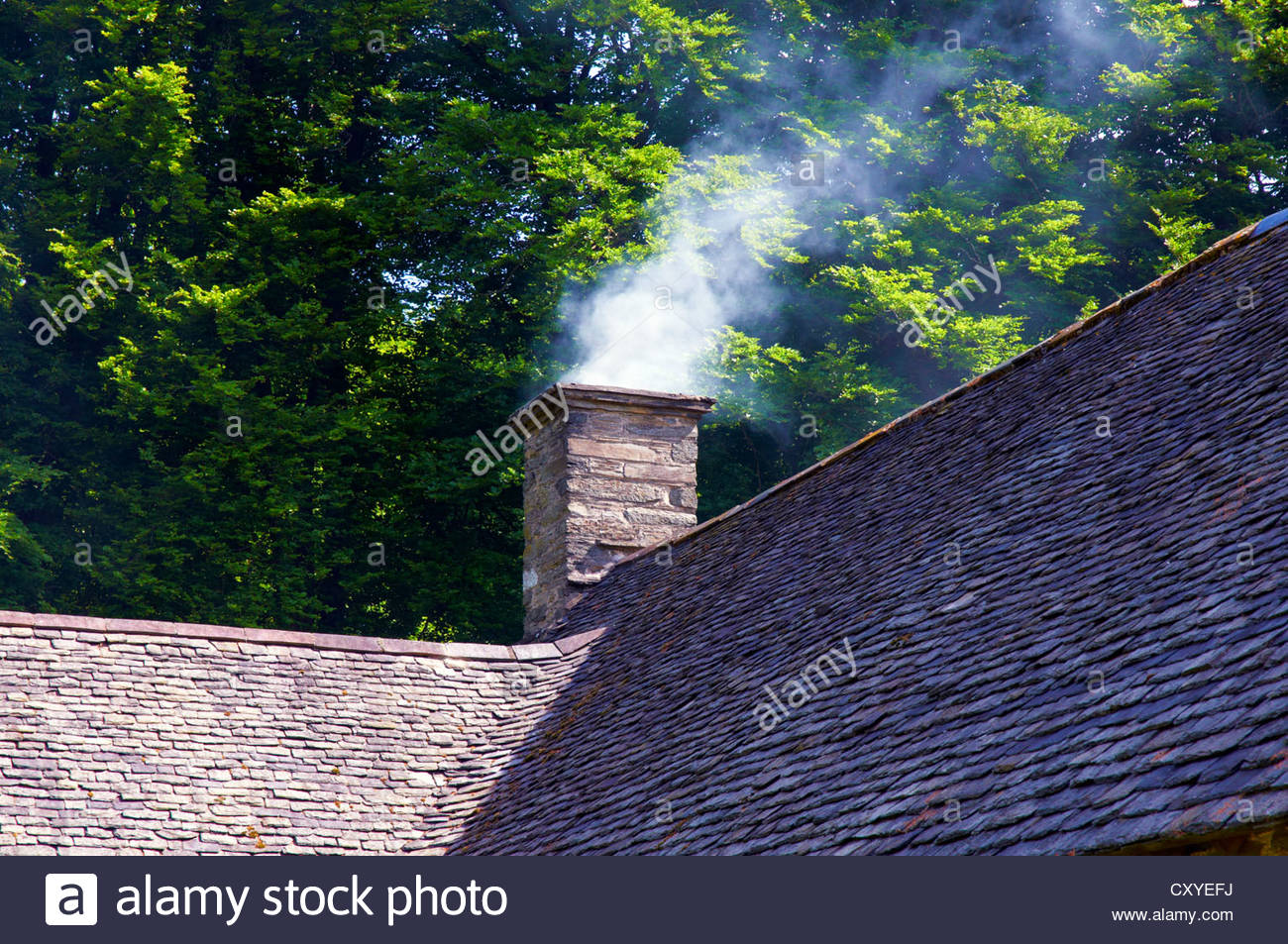 smoke being emitted from a chimney stack on a tiled roof Stock Photo