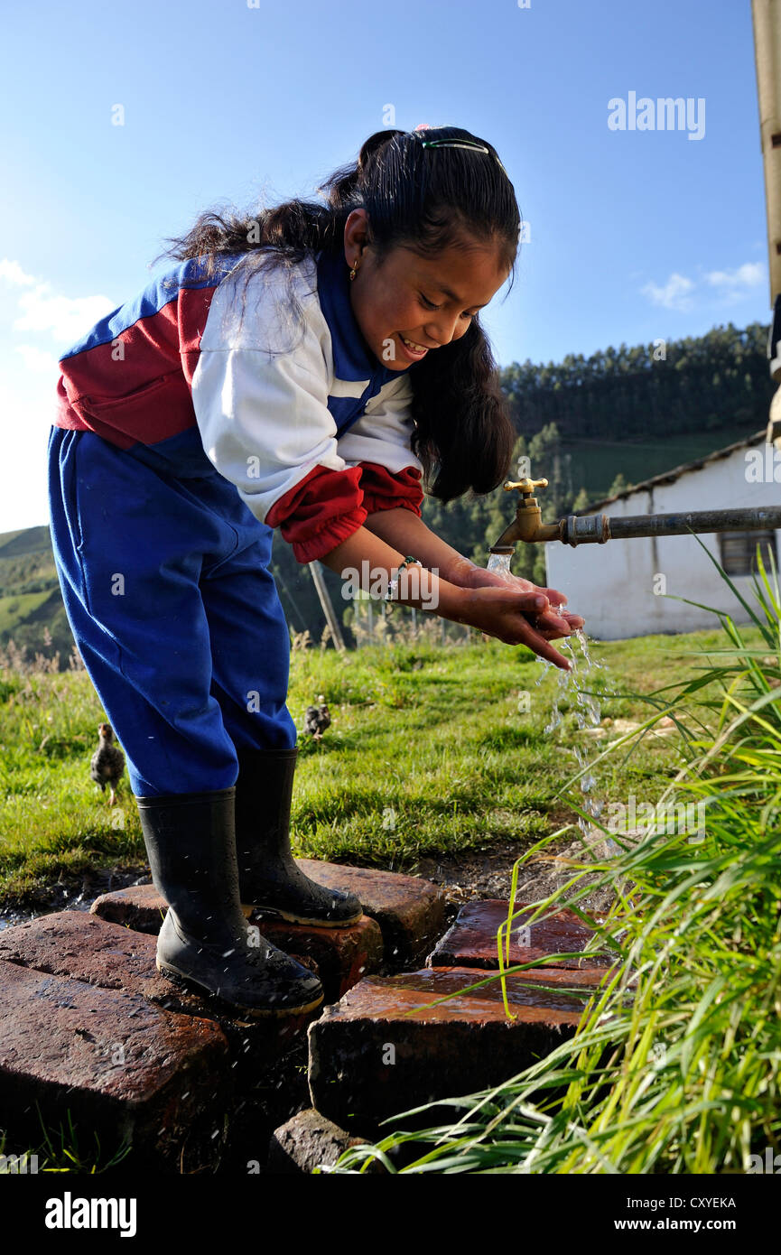 Girl washing her hands at a tap next to her house, her family has been connected to the fresh water infrastructure - Stock Image