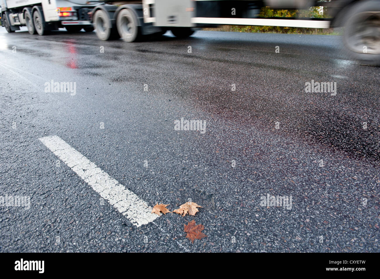 Truck driving on treacherous and slippery road due to rain or frost Stock Photo