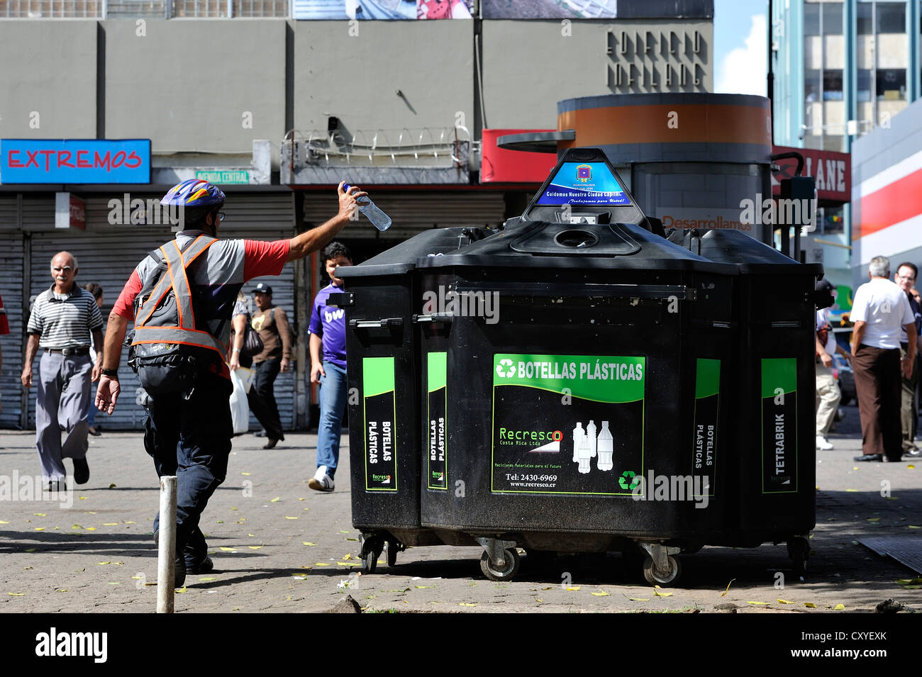 Man throwing a plastic bottle into a container for recyclables, waste separation and recycling, pedestrian zone - Stock Image