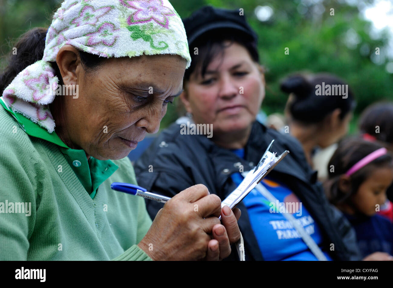 Woman signing an attendance sheet, the aid organisation provides health services and education for mothers and children - Stock Image
