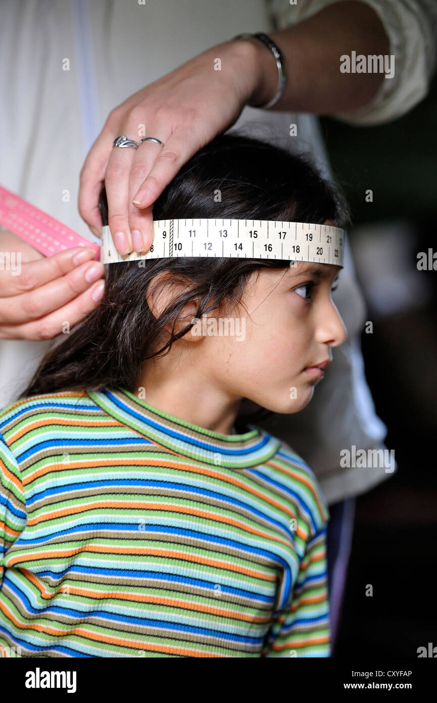 Worker of an aid organisation measuring the circumference of a girl's head, to track her physical development, - Stock Image