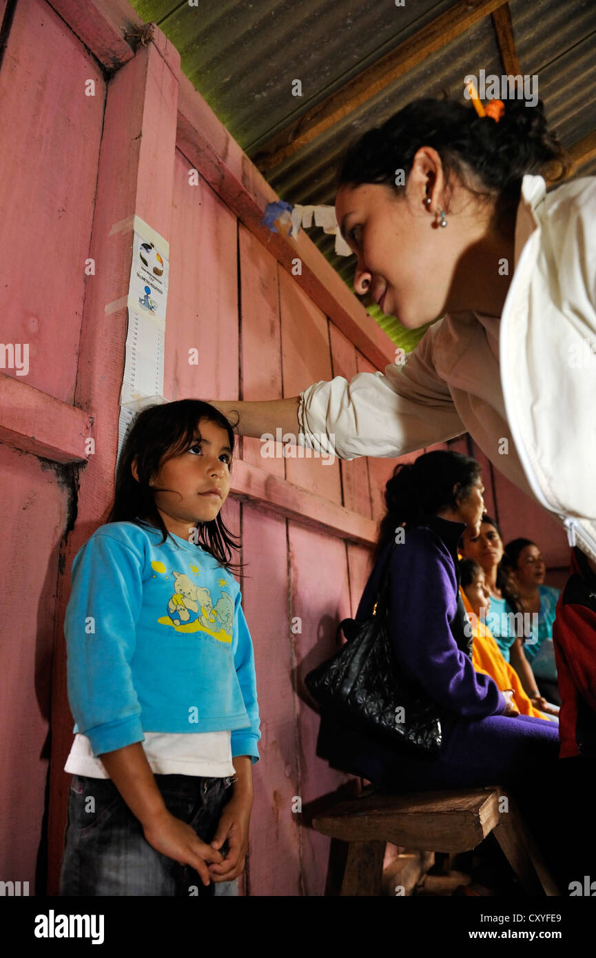 The height of a girl is being measured, an aid organisation examining children in a rural community, Comunidad Martillo - Stock Image