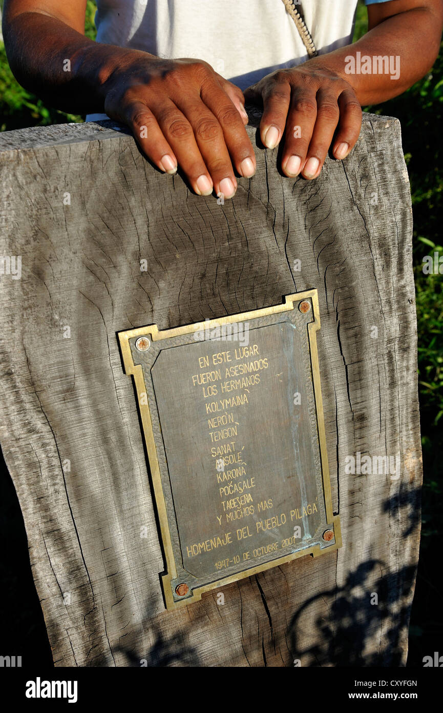 Leader of the Onedi village standing next to a memorial plaque that commemorates the massacre of their people in - Stock Image