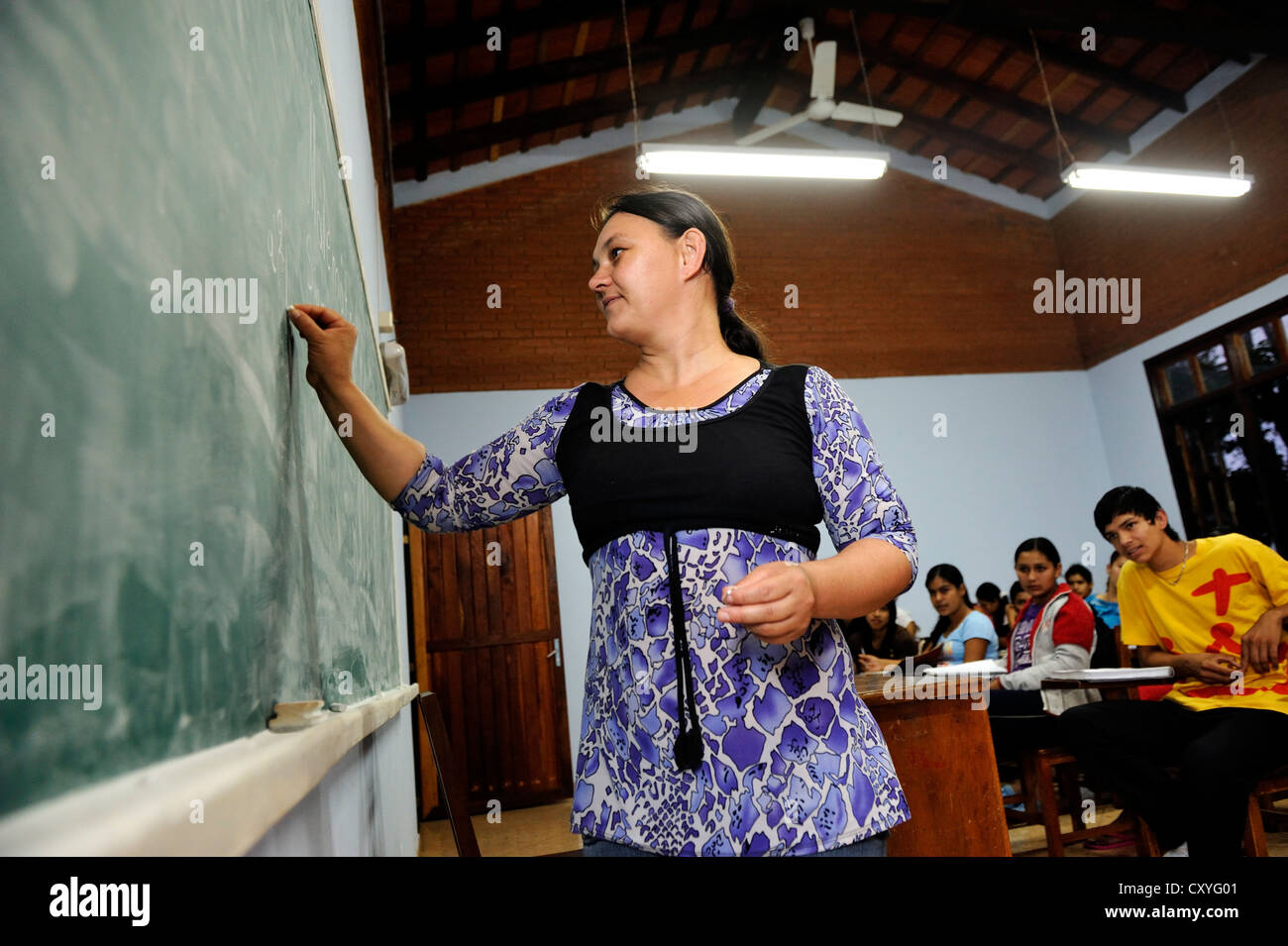 Young female teacher writing on a blackboard, lessons at the agricultural college CECTEC, Itapua, Paraguay, South - Stock Image
