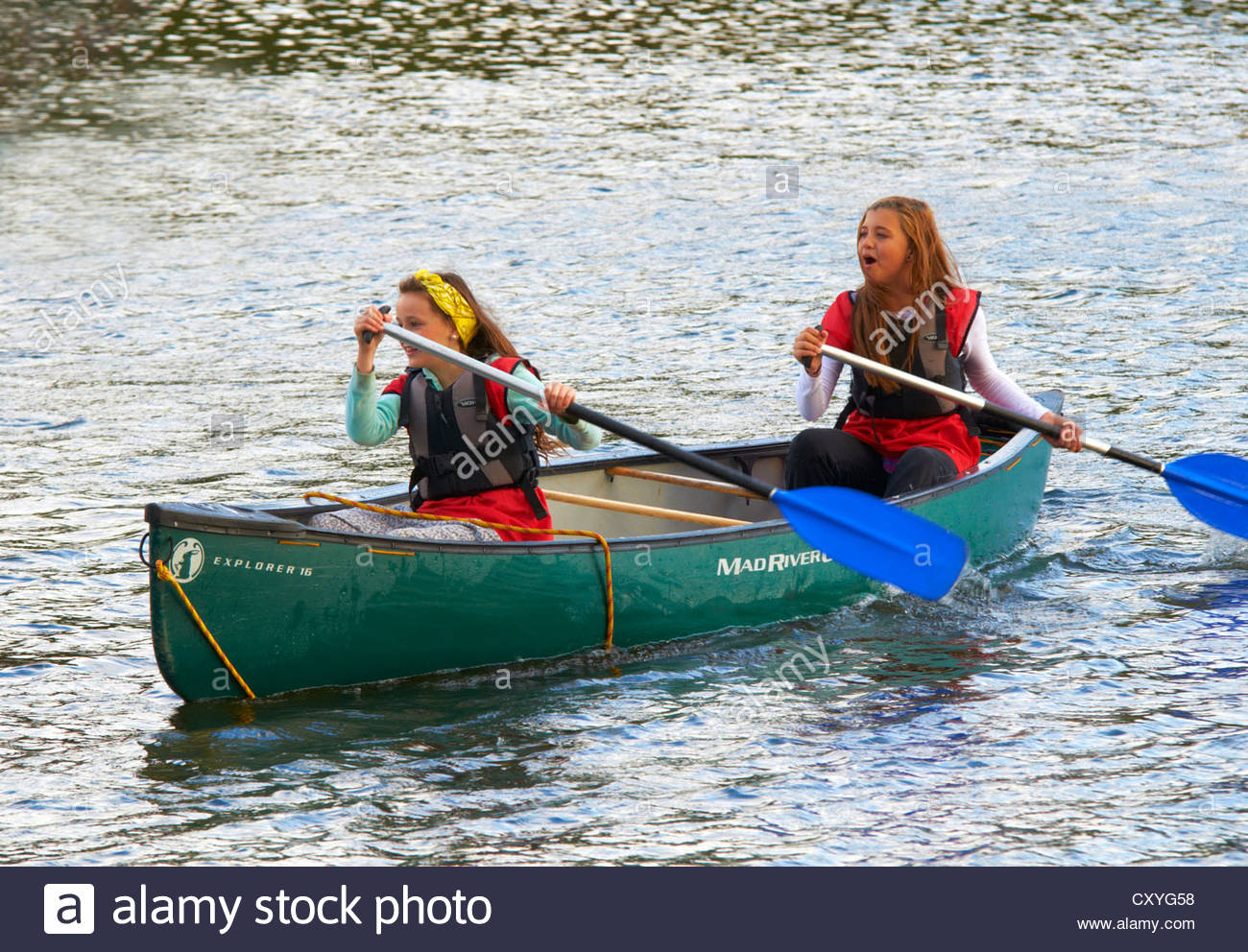 two teenage girls 13 - 15 rowing a canoe and having fun on the water - Stock Image