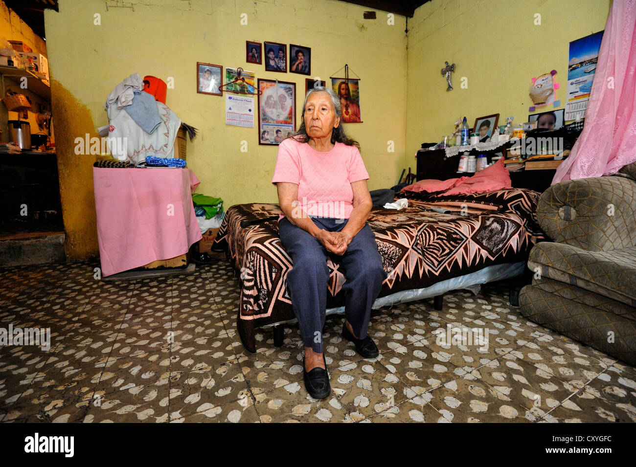 Old woman sitting in her humble apartment, El Esfuerzo slum, Guatemala City, Guatemala, Central America - Stock Image