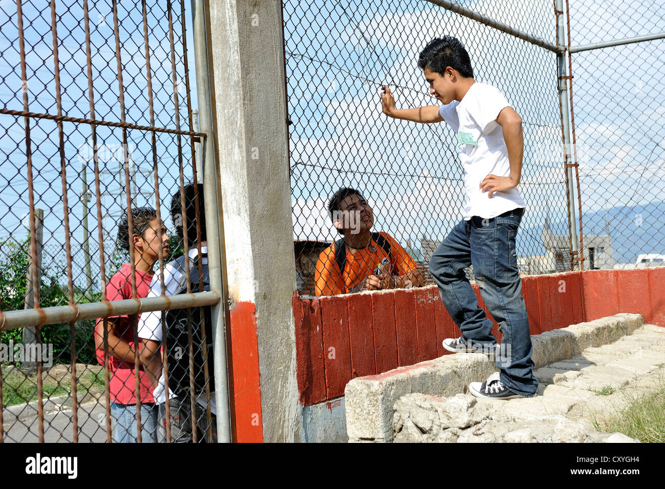 Teenager, 16 years old, talking to his friends on the street through a chain link fence, Escuela Ceiba school - Stock Image