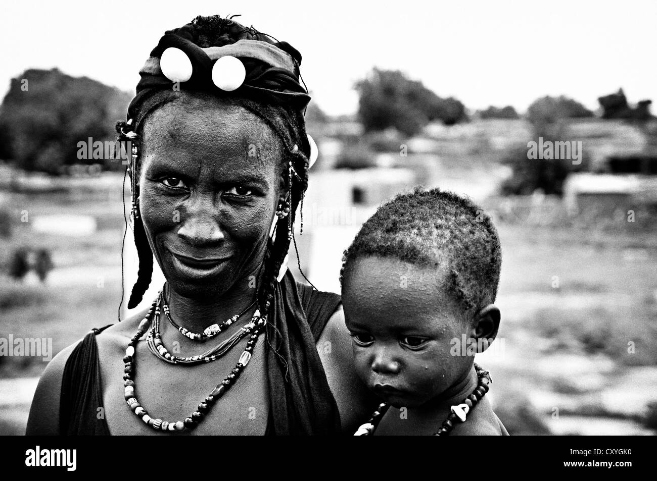 Peul woman wearing handmade jewelry with her baby, Mali Stock Photo
