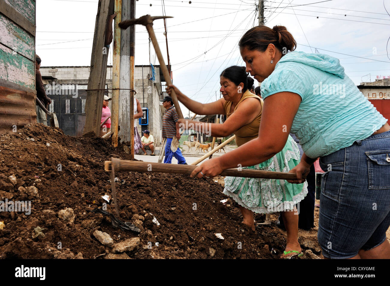 Women working together to improve the sewer system of their neighborhood, Lomas de Santa Faz slum, Guatemala City, - Stock Image