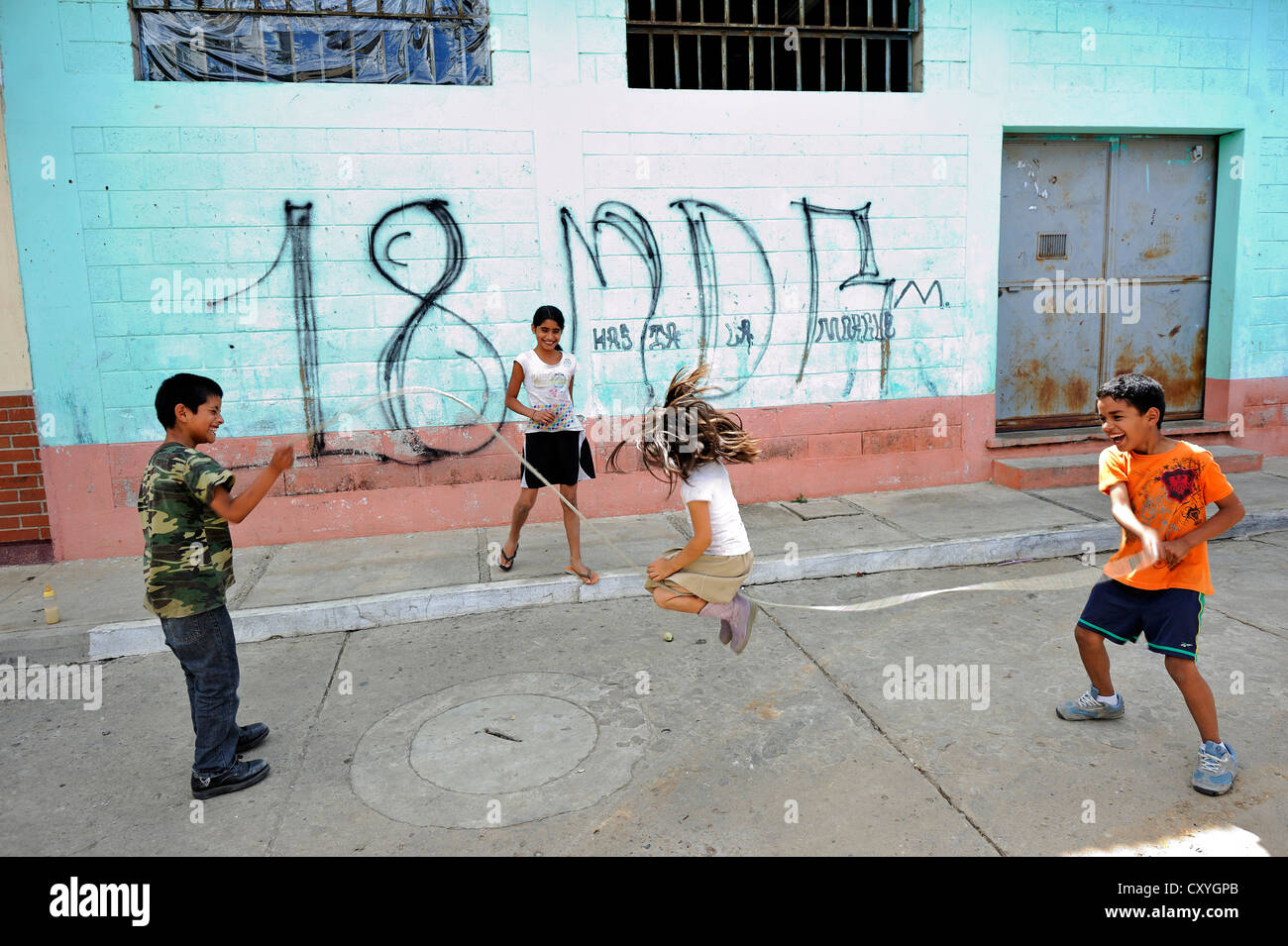 Children playing in front of a wall with graffiti of the criminal Mara 18 gang of youths, Lomas de Santa Faz slum - Stock Image