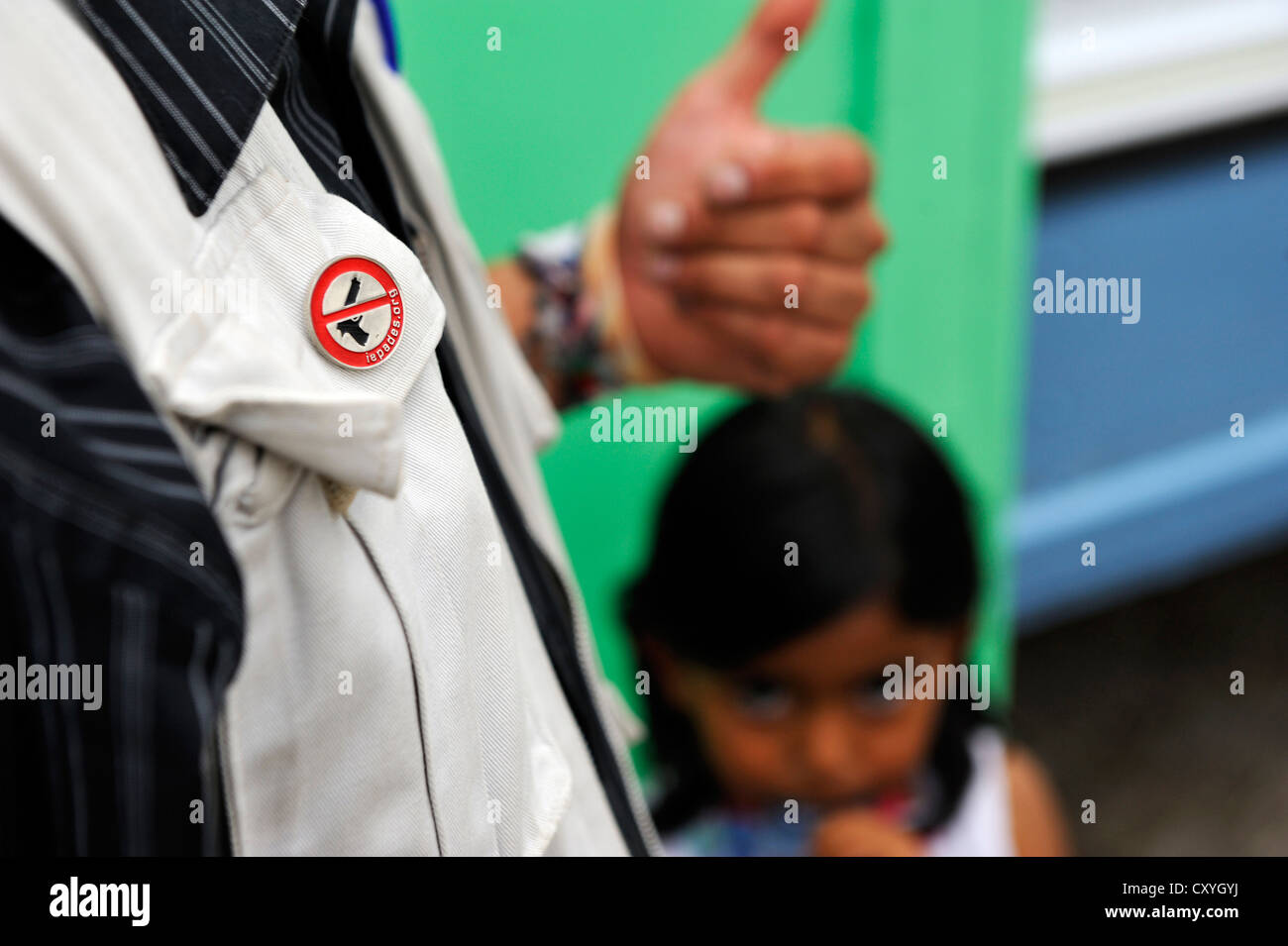 'No Weapons' pin on the jacket of a peace worker of the human rights organization El Ceiba; They are travelling - Stock Image