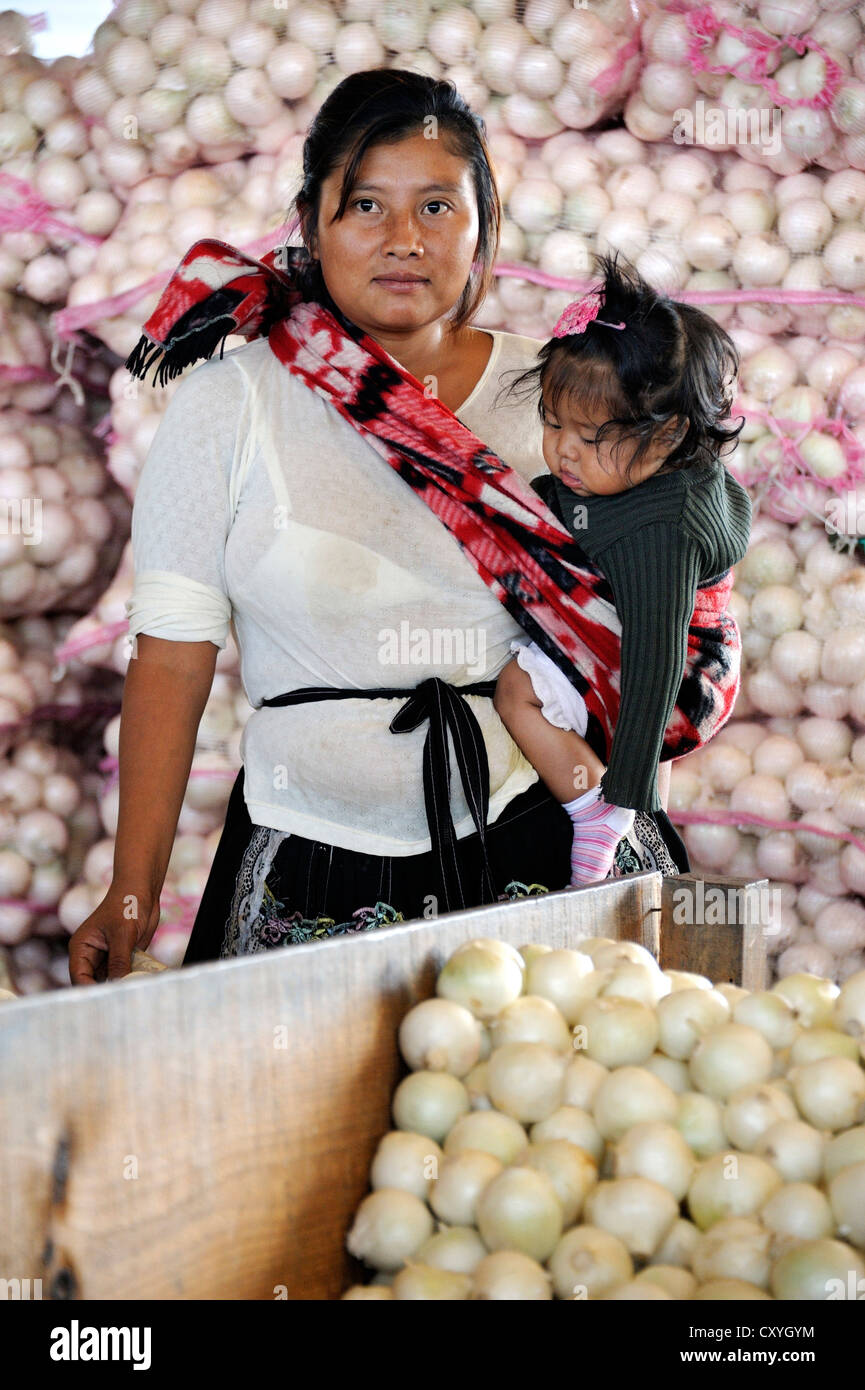Indigene woman carrying a small girl in a sling, standing in front of bags of onions, CENMA, vegetable wholesale - Stock Image