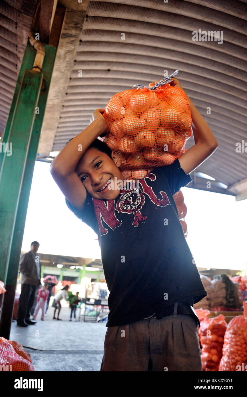 Child labor, boy carrying a bag of onions, CENMA, vegetable wholesale market in the south of Guatemala City, Guatemala - Stock Image