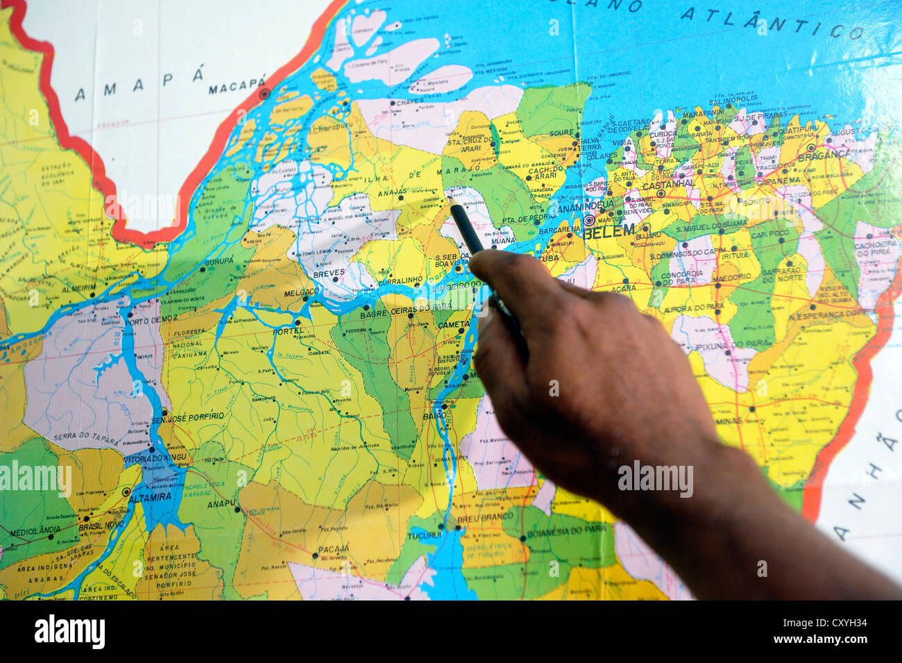 Hand pointing towards a map with a pen towards a location in the