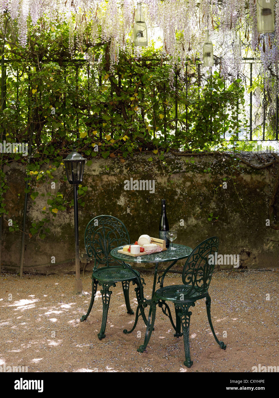 Still life, cheese buffet on an round, antique cast-iron garden table with two chairs in a romantic courtyard Stock Photo