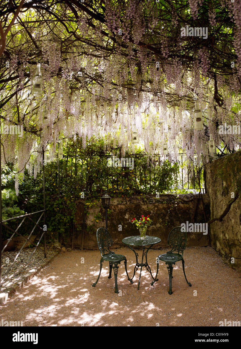 Round, cast-iron garden bistro table with two chairs in a romantic backyard Stock Photo