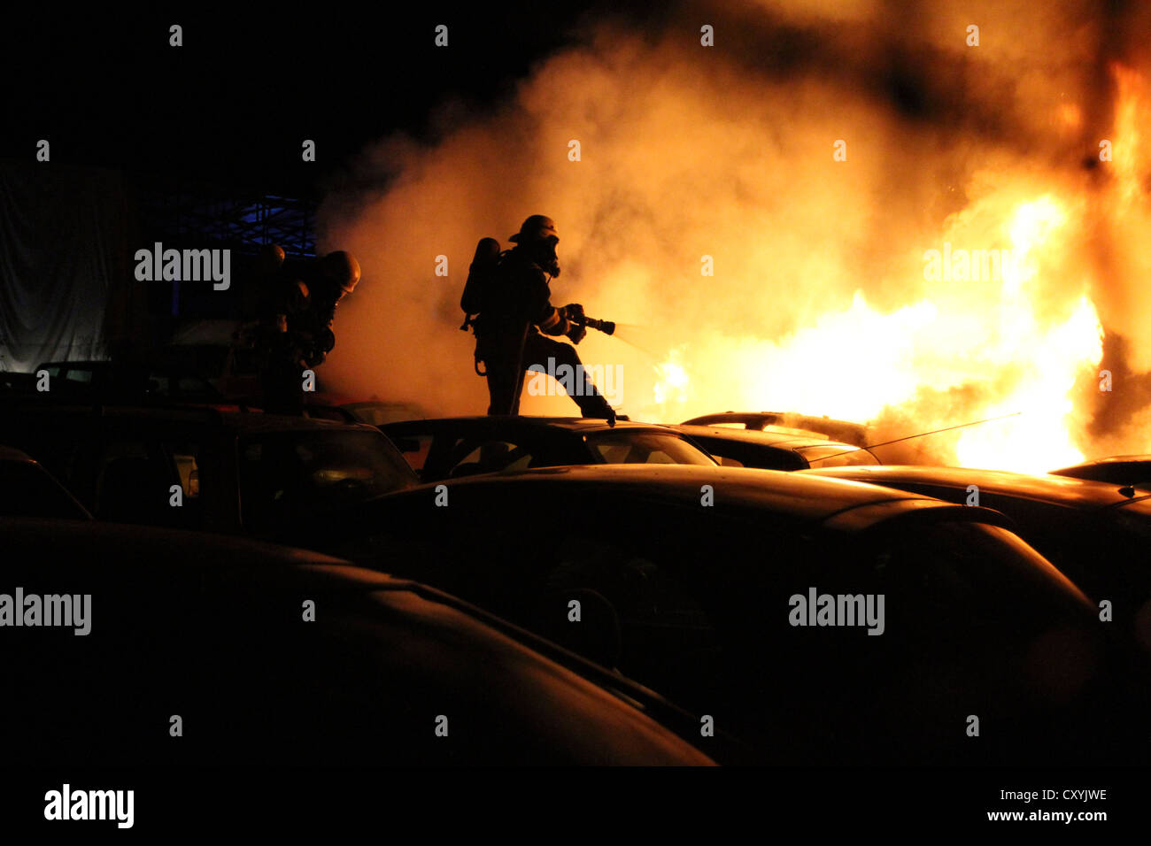 Arson attach on cars, firefighters trying to extinguish burning cars in the car park of a car dealer in Berlin-Schmoeckwitz - Stock Image