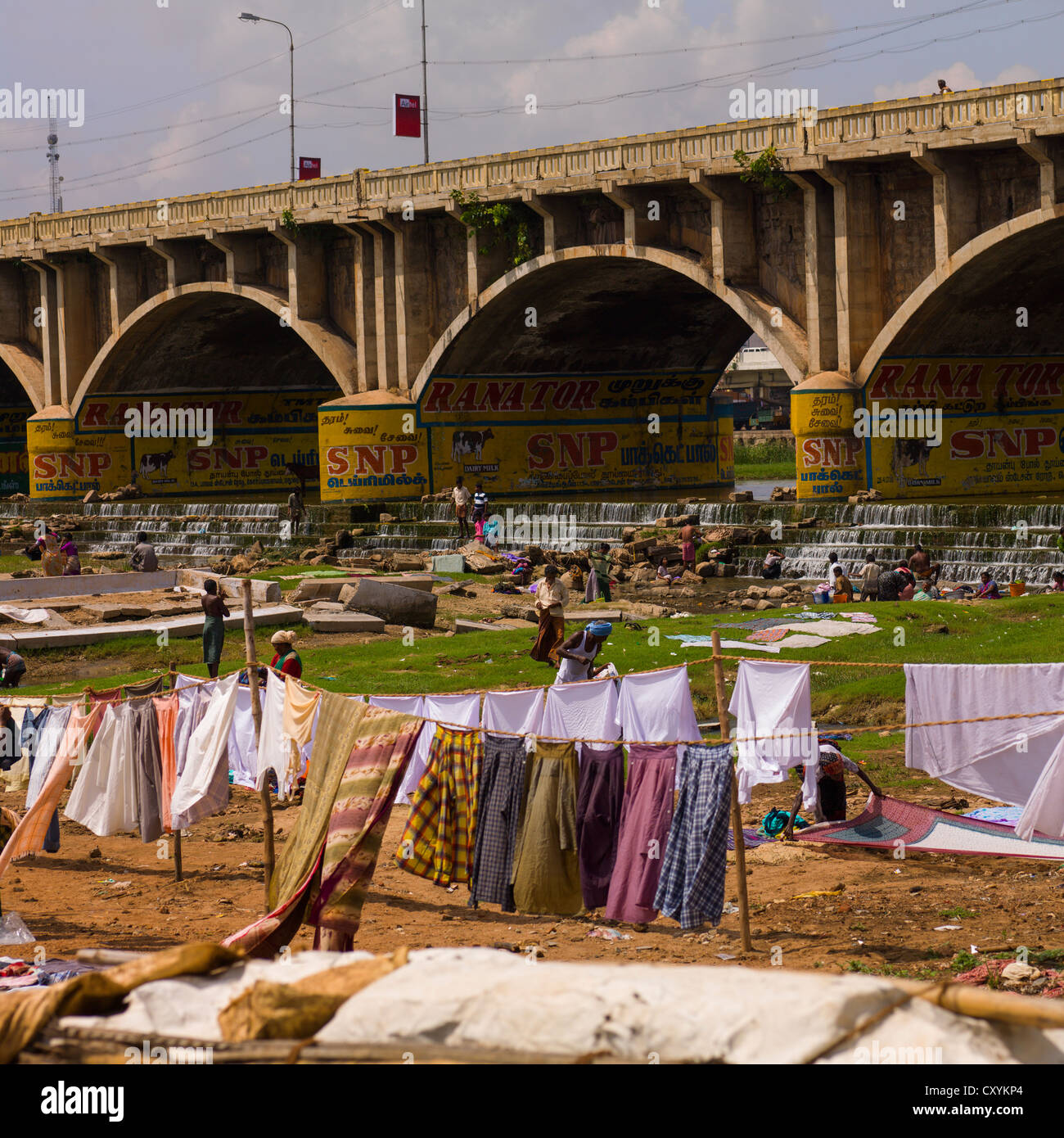 People Washing And Putting Dry Clothes Under A Painted Bridge, Madurai, India - Stock Image