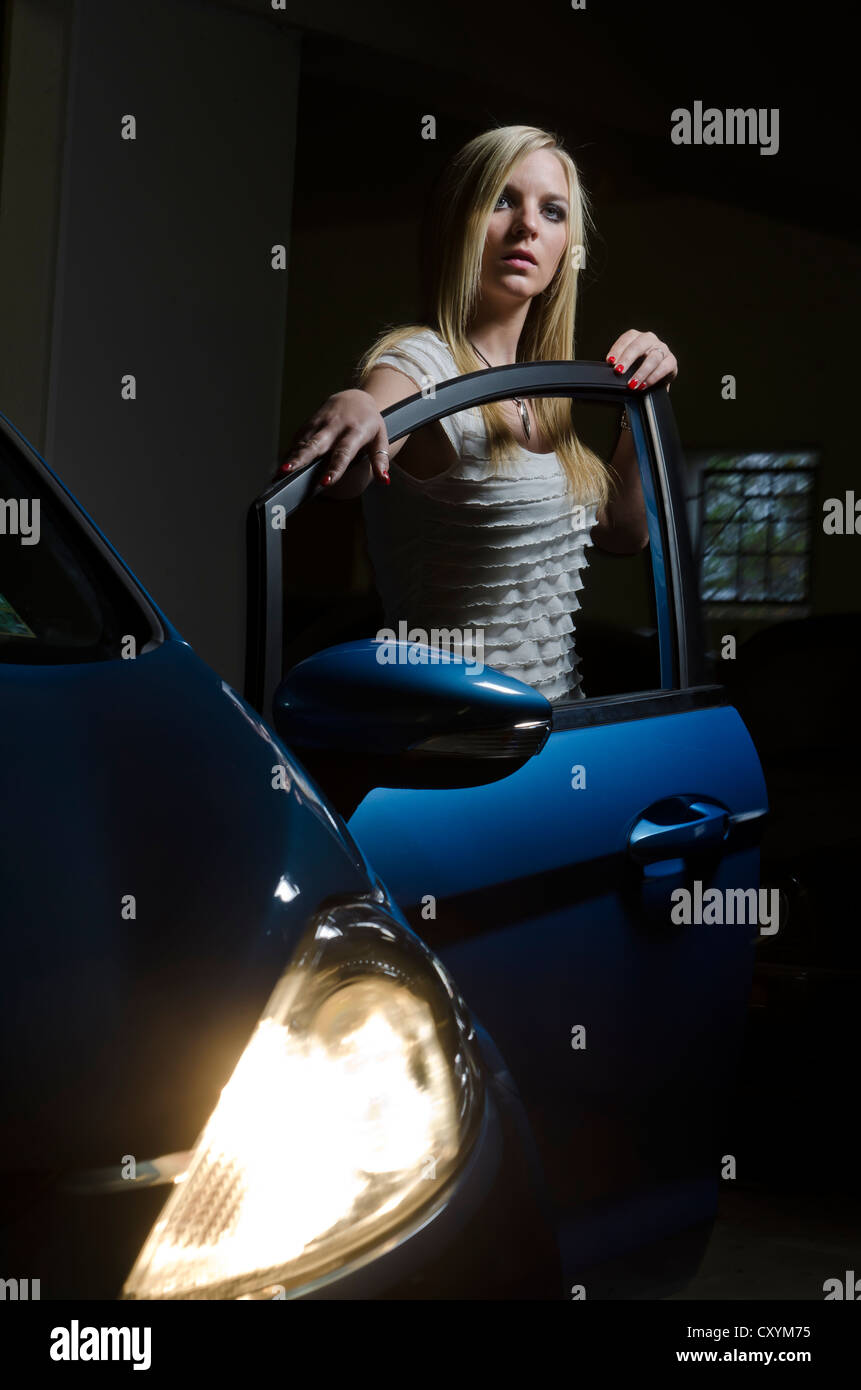 Young woman, 23, standing at the open driver's door of a car, underground car park - Stock Image