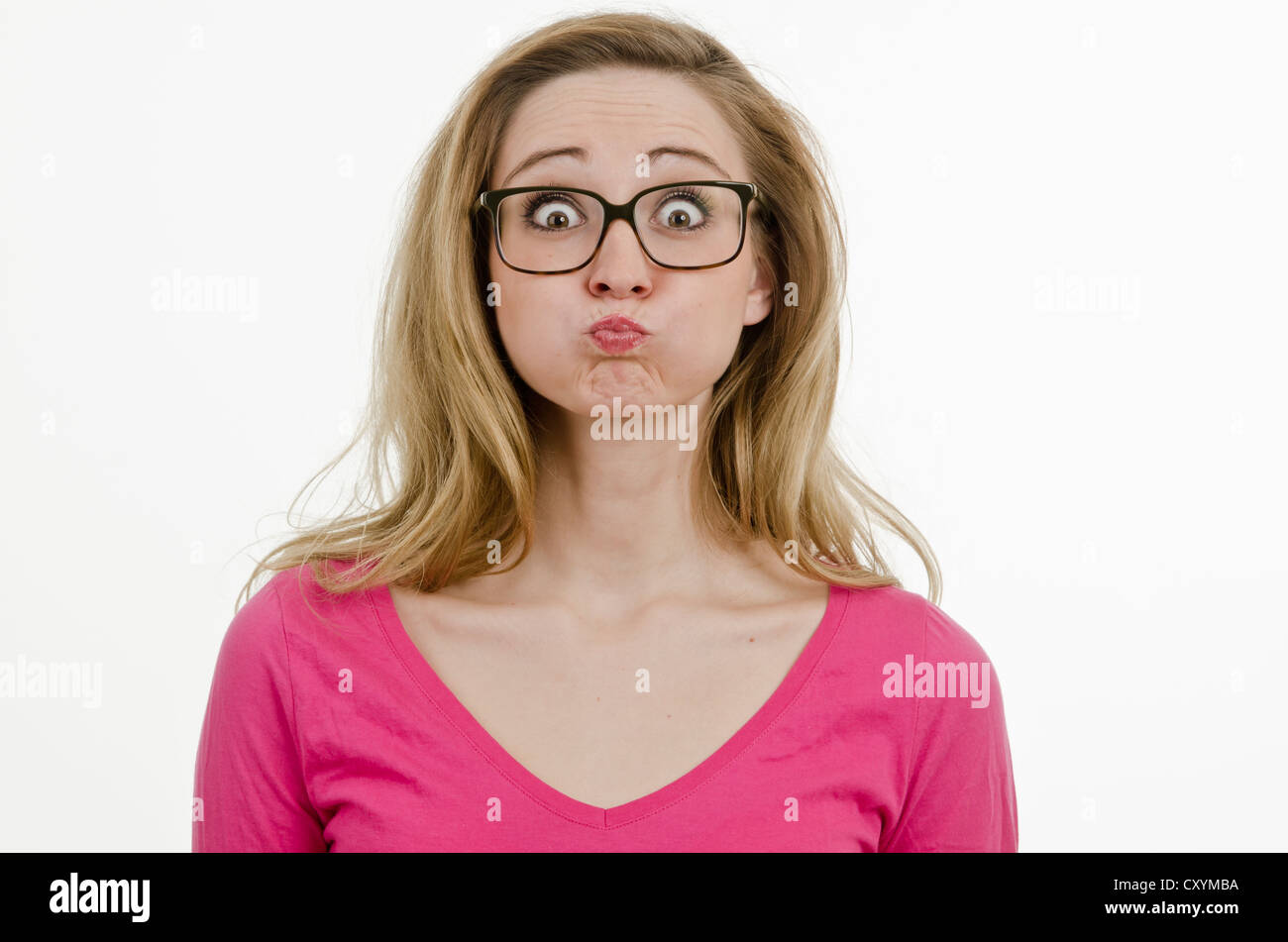 Young woman, 25, wearing large glasses, with puffed cheeks and her eyes wide open - Stock Image