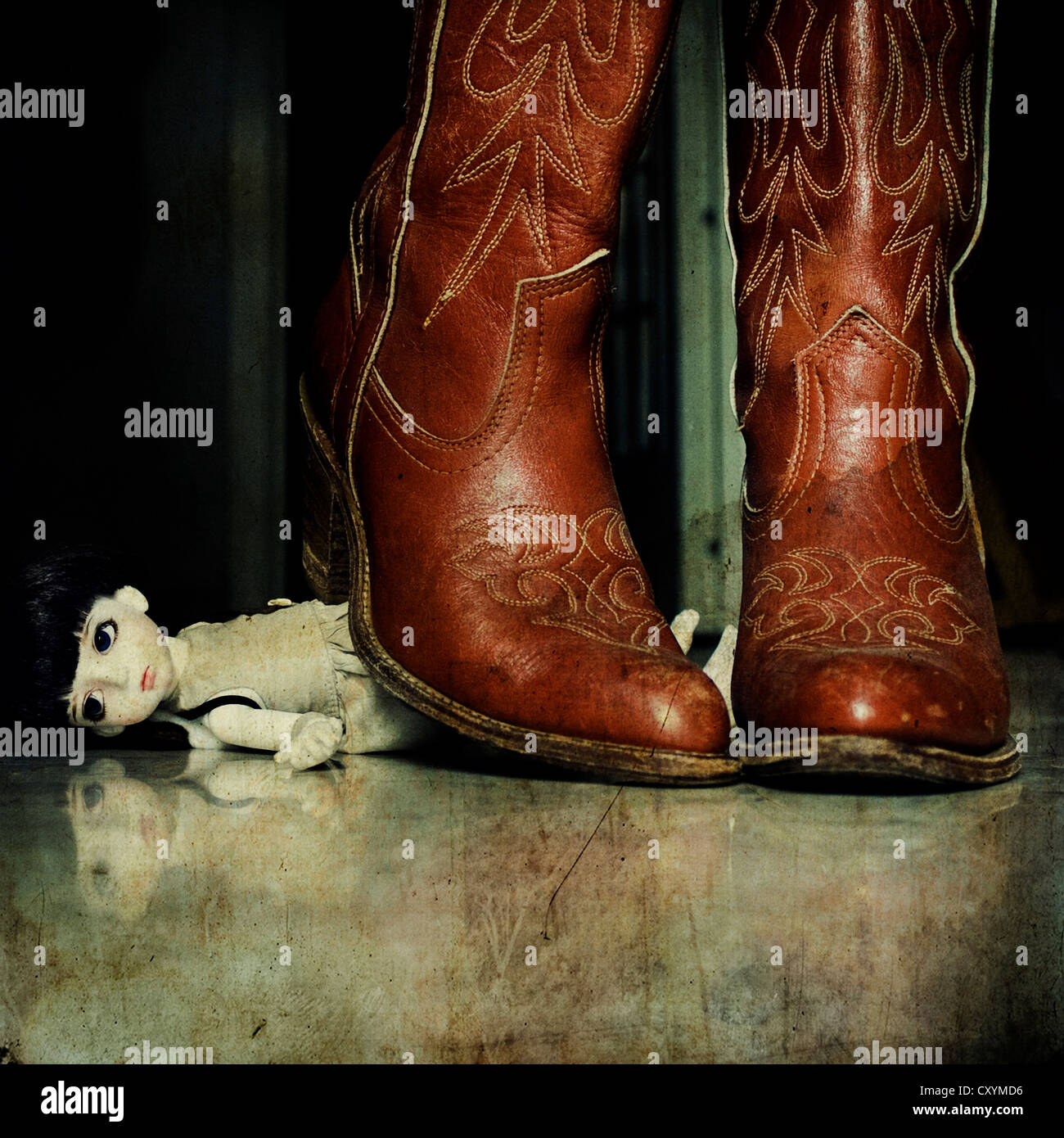 a pair of cowgirl boots over a little doll - Stock Image