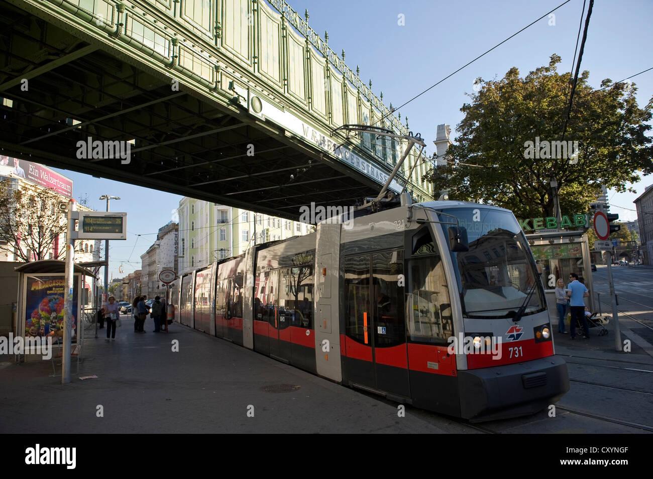 Electric Tram beneath a rail bridge at Wahringer Strasse, Vienna, Austria. Stock Photo