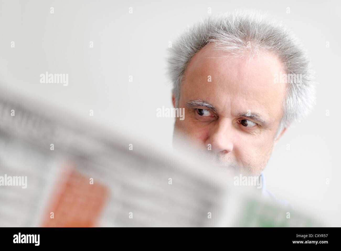 A man reading a newspaper, being astonished, North Rhine-Westphalia - Stock Image